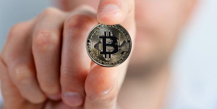 en-man-håller-i-en-bitcoin