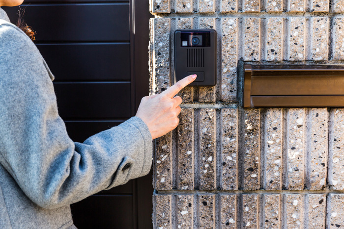 female hand pushing doorbell buzzer